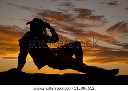 A silhouette of a cowboy pushing up off the ground with his arm and holding on to his hat. - stock photo