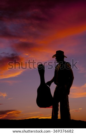 A silhouette of a cowboy standing and holding on to his guitar case.