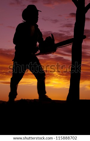 a silhouette of a cowboy with a chainsaw cutting a tree down - stock photo