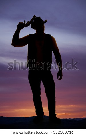 a silhouette of a cowboy with a pistol up by his western hat. - stock photo