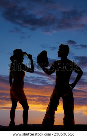a silhouette of a cowboy with his cowgirl in the outdoors. - stock photo