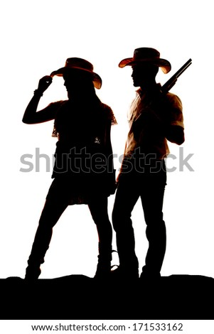 a silhouette of a cowgirl and a cowboy.  He is holding onto a gun. - stock photo