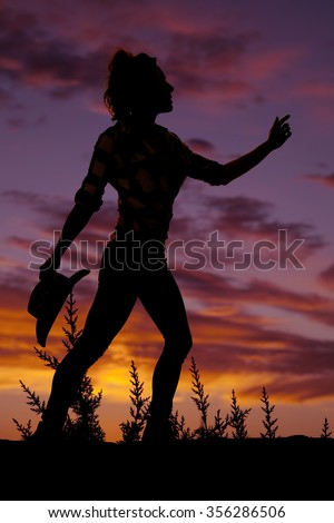 a silhouette of a cowgirl holding on to her western hat reaching forward. - stock photo