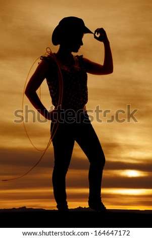 a silhouette of a cowgirl holding on to the brim of her hat. - stock photo