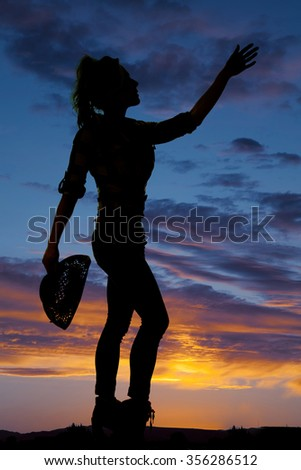 a silhouette of a cowgirl holding up her hand reaching to the sky. - stock photo