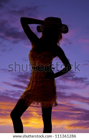 a silhouette of a cowgirl in her lace dress and cowgirl hat. - stock photo