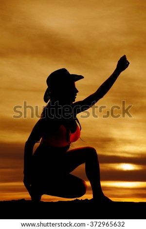 A silhouette of a cowgirl on one knee reaching up. - stock photo