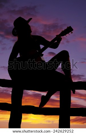 A silhouette of a cowgirl sitting on a fence playing her guitar. - stock photo