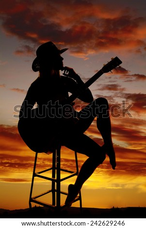 A silhouette of a cowgirl sitting on a stool holding her guitar thinking. - stock photo