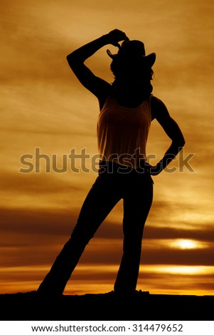 a silhouette of a cowgirl with her hand on her western hat. - stock photo
