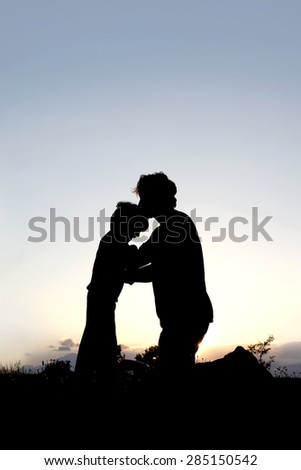 A silhouette of a Father lovingly kissing his young child on the head at sunset. - stock photo