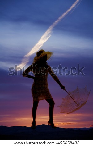 A silhouette of a girl with her umbrella pointing it to the ground.
