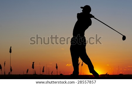 a silhouette of a golfer on a bright sky - stock photo