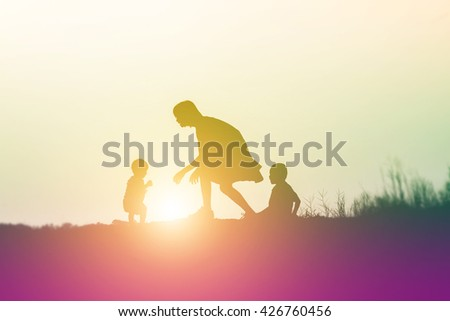 a silhouette of a happy young girl child the arms of his loving