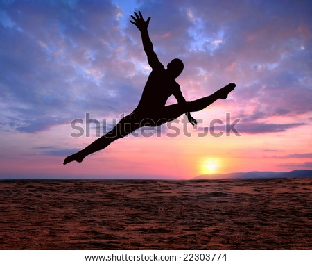 A silhouette of a jumping man on a colorful sunset background - stock photo