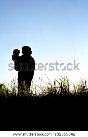 A silhouette of a loving young father holding his happy toddler child, while standing in grass outside in the evening.  Room in sky for copy-space. - stock photo