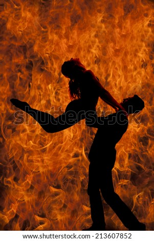 A silhouette of a man and woman dancing, he is doing a lift, with a background of fire. - stock photo