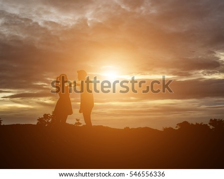 a silhouette of a man and woman holding hands with each other, walking together.
