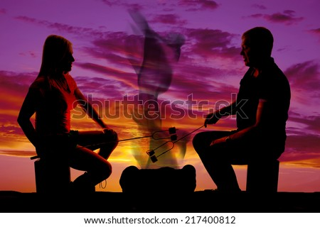 A silhouette of a man and woman in the outdoors, roasting marshmallows. - stock photo