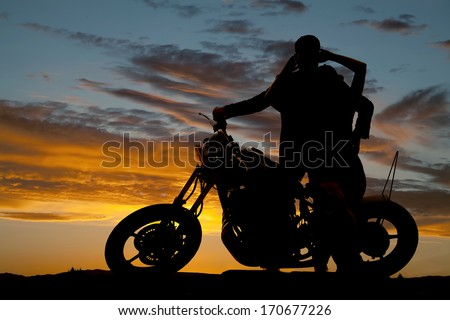 A silhouette of a man and woman next to a motorcycle holding each other. - stock photo