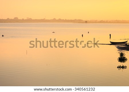 A silhouette of a man fishing and boats at sunset in Mandalay , Myanmar .Near u-bein bridge at Taungthaman Lake.  - stock photo