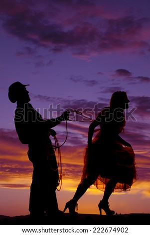 A silhouette of a man  holding on to a rope that is around his lady. - stock photo