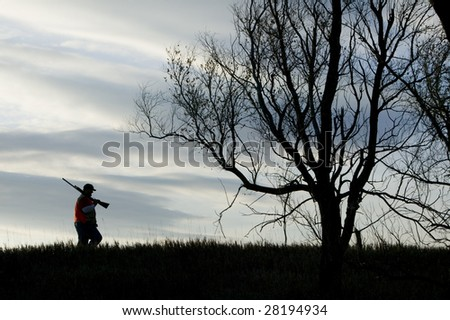 A silhouette of a man hunting - stock photo