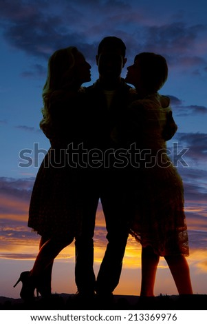 a silhouette of a man inbetween two women in the outdoors. - stock photo