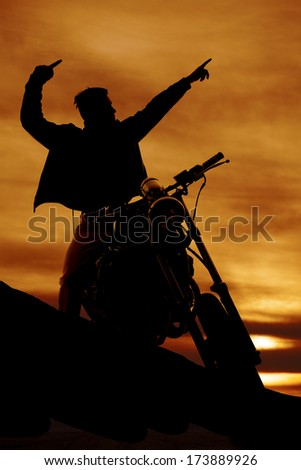 a silhouette of a man on a motorcycle pointing.