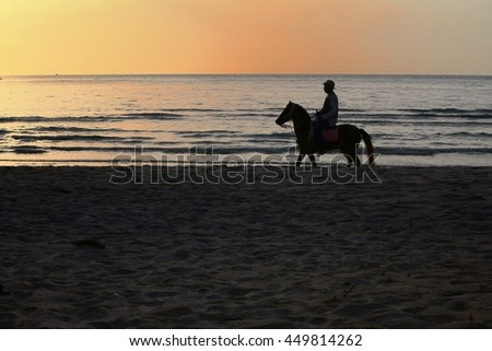 A silhouette of a man riding horse by the beach with the sunrising sky