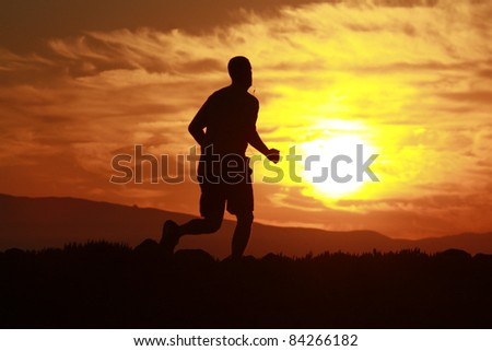 A silhouette of a man running on a trail with with the sun ricing up in the morning - stock photo