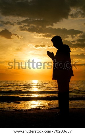 A silhouette of a man standing at the ocean with his hands folded in prayer with a beautiful sunset behind him. - stock photo