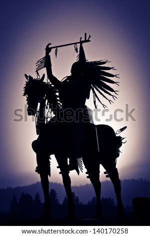 A silhouette of a Native American on a horse made from metal with distant mountains and a purple haze vignetting.
