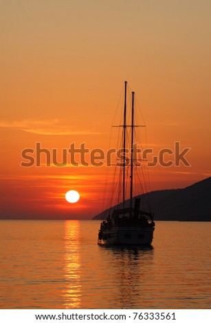 A silhouette of a sailboat in the sunset - stock photo