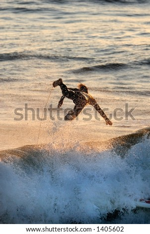 A silhouette of a surfer flying through the air. - stock photo