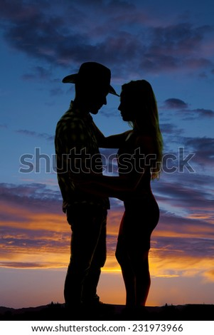 A silhouette of a woman and her cowboy holding each other in the outdoors. - stock photo