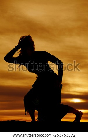 A silhouette of a woman crouching down walking in the outdoors. - stock photo