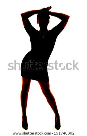 A silhouette of a woman dancing in her skirt and heels. - stock photo