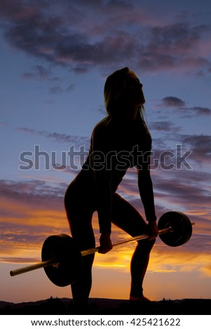 a silhouette of a woman doing a dead lift in the outdoors, with a barbell. - stock photo