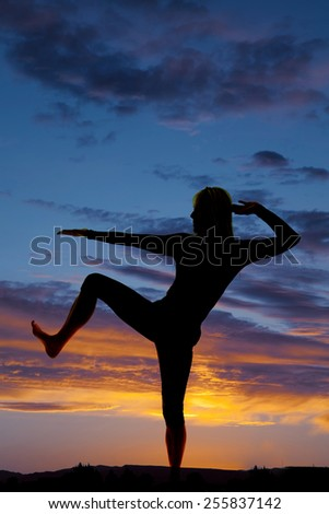 A silhouette of a woman doing a kick and stretch in the outdoors. - stock photo