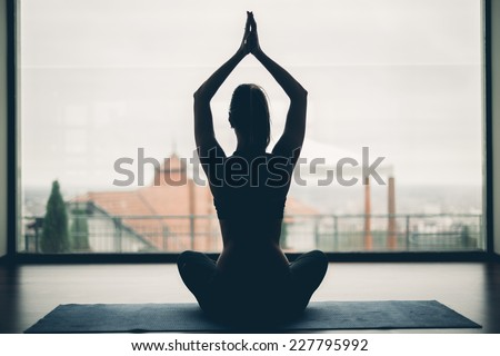 A silhouette of a woman doing yoga - stock photo