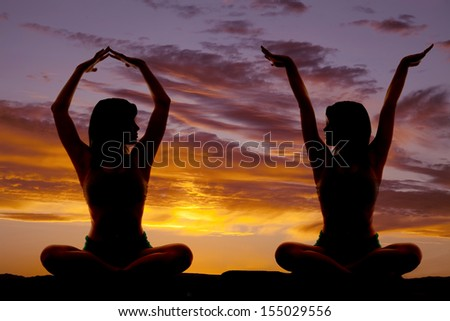 A silhouette of a woman doing yoga with her arms meditating.