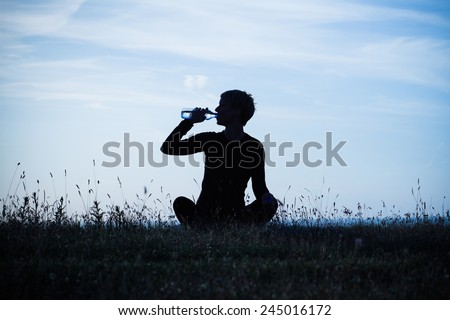 A silhouette of a woman drinking water after exercise,intentionally toned image.Refreshment after exercise - stock photo
