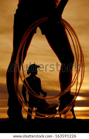 A silhouette of a woman holding on to a rope with a cowboy in between her legs. - stock photo