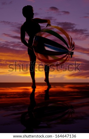 A silhouette of a woman holding on to her beach ball. - stock photo