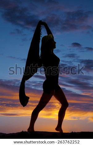 A silhouette of a woman holding on to her sarong stepping and dancing. - stock photo