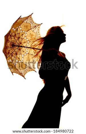 A silhouette of a woman holding on to her umbrella. - stock photo