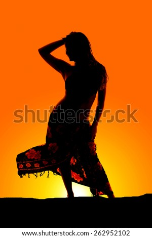 A silhouette of a woman in her bikini and her sarong in the outdoors, - stock photo