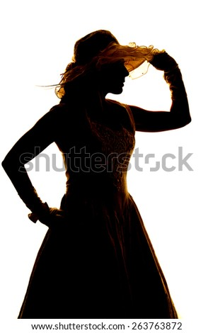 a silhouette of a woman in her dress, touching the brim of her hat.