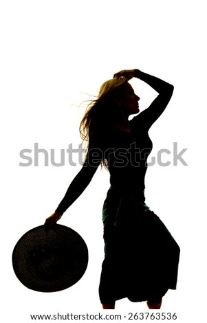 a silhouette of a woman in her dress with her hand in her hair and a hat in her other hat. - stock photo